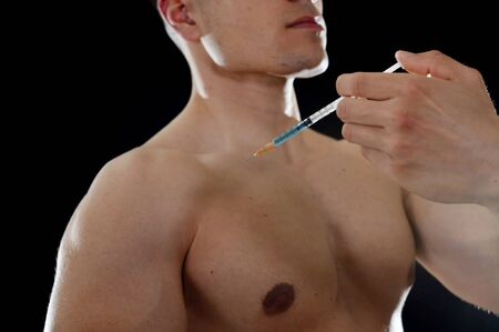 hormones: young body building sportsman using steroids for increasing sport and athletic  performance injecting syringe in shoulder in sport cheat doping and illegal use of hormones
