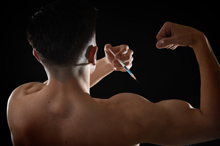 steroids: young body building sportsman using steroids for increasing sport and athletic  performance injecting syringe in shoulder in sport cheat doping and illegal use of hormones