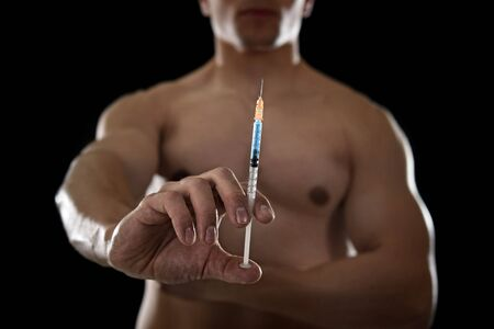 steroids: young body building sportsman using steroids for increasing sport and athletic  performance holding close up syringe isolated on back background in sport cheat doping and illegal use of hormones Stock Photo