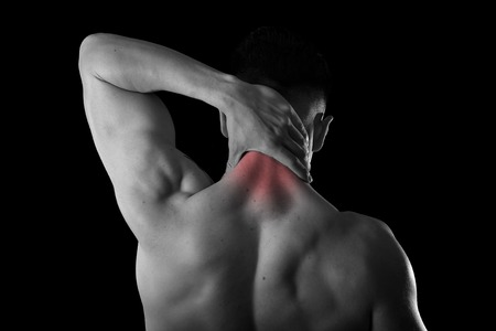 back of young muscular sport man holding sore neck with hand touching or massaging cervical area suffering body pain in spine back health problem isolated black and white red spot injury