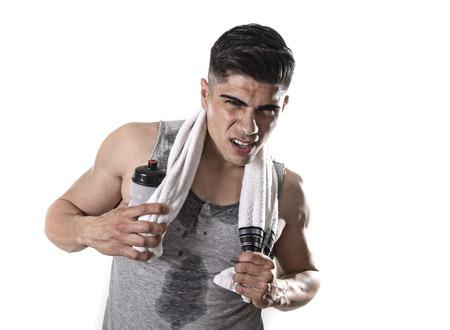 body expression: joven hombre de deporte cansada con cuerpo en forma atl�tica sosteniendo la toalla y botella de agua en la expresi�n de la cara agotada para respirar despu�s de un entrenamiento duro entrenamiento empapado de sudor aislado en el fondo blanco