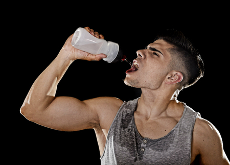 sweaty: close up portrait of young athletic sport man thirsty drinking water holding the bottle pouring the fluid on his sweaty face refreshing and recovering after hard training workout in hydration concept