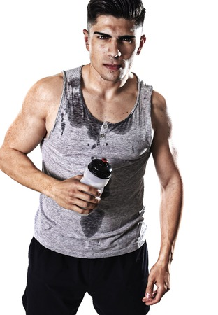 hydration: portrait of young athletic sport man thirsty holding bottle of water  with sweaty face and wet singlet after refreshing and recovering after hard training workout in hydration concept