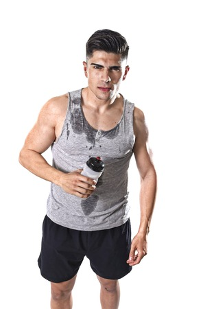 sweaty: portrait of young athletic sport man thirsty holding bottle of water  with sweaty face and wet singlet after refreshing and recovering after hard training workout in hydration concept