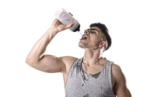 close up portrait of young athletic sport man thirsty drinking water holding the bottle pouring the fluid on his sweaty face refreshing and recovering after hard training workout in hydration concept