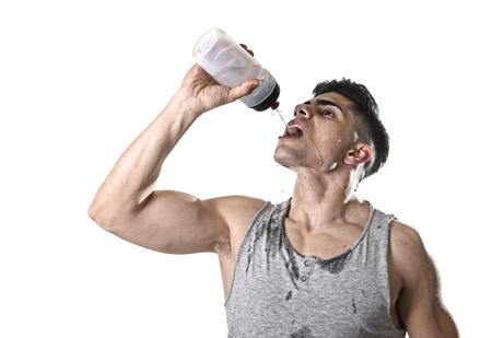 若い運動スポーツ男のどが渇いて水を飲んでリフレッシュし、水分補給概念でハード トレーニング トレーニング後の回復彼の汗まみれの顔に液体を注いで瓶を保持しているの肖像画間近します。