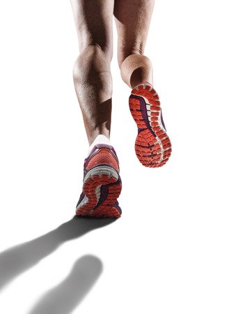 high performance: rear view close up strong athletic female legs and running shoes of sport woman jogging isolated in fitness healthy lifestyle high performance and endurance concept in advertising style Stock Photo