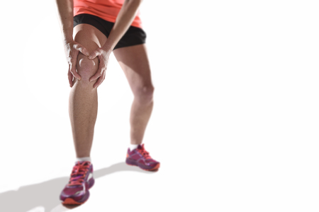 contracture: young sport woman with strong athletic legs holding knee with his hands in pain after suffering ligament injury during a running workout training isolated  white background