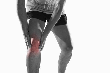 contracture: young sport woman with strong athletic legs holding knee with his hands in pain after suffering ligament injury during a running workout training isolated  background in black and white with red spot