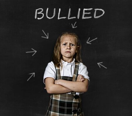 bullied: young sweet junior schoolgirl victim of bully crying sad standing in front of school class blackboard with chalk text bullied in school children bullying problem and education stress concept