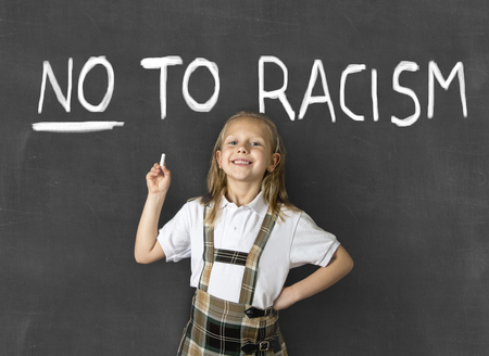 anti racist: young sweet junior schoolgirl with blonde hair smiling happy isolated in front of classroom blackboard holding chalk in no to racism anti racist education and world diversity and peace concept