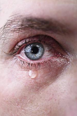 close-up van de blauwe ogen van de man huilen in tranen bedroefd en vol pijn in depressie tragiek en tragische probleem begrip Stockfoto