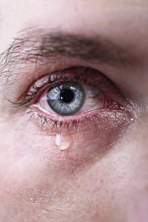 close up of blue eye of man crying in tears sad and full of pain in depression tragedy and tragic problem concept