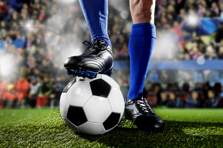 flare up: close up legs and feet of football player in blue socks and black shoes standing  with the ball playing match at soccer stadium on green grass pitch with audience flash lights and flare Stock Photo