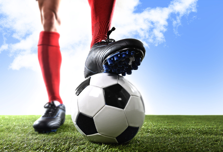 shocks: close up legs and feet of football player in red shocks and black shoes posing with the ball standing on grass outdoors isolated on blue sky background Stock Photo