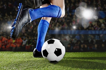 dribbling: close up legs and feet of football player in action wearing blue socks and black shoes running and dribbling with the ball playing match on green grass pitch at  soccer stadium with flashes and flares