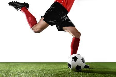 legs  white: close up legs of football player in red socks and black shoes running and kicking the ball in free kick action playing isolated on white background