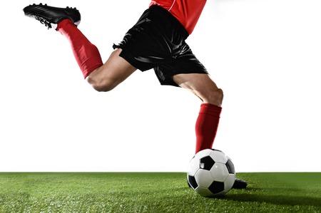 bonhomme blanc: fermer les jambes du joueur de football dans des chaussettes rouges et des chaussures noires en cours d'exécution et de coups de pied la balle dans l'action du coup franc jouant isolé sur fond blanc