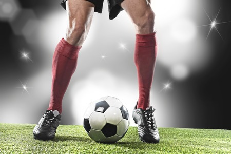 dribbling: close up legs and feet of football player in red socks and black shoes running and dribbling with the ball playing on stadium pitch with background flashes and light flares Stock Photo