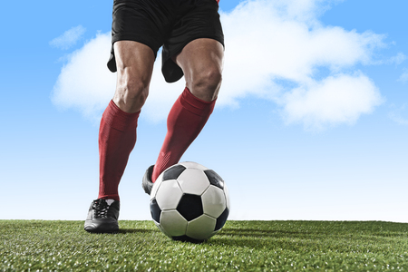 dribbling: close up legs and feet of football player in red socks and black shoes running and dribbling with the ball playing outdoor on green grass pitch under a blue sky