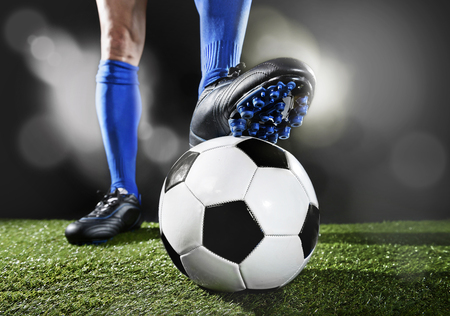 flare up: close up legs and feet of football player in blue socks and black shoes playing  with the ball standing on green grass pitch isolated on black background with flash lights and lens flare