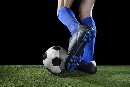 dribbling: close up legs and feet of football player in action wearing blue socks and black shoes running and dribbling with the ball playing on green grass pitch isolated on black background