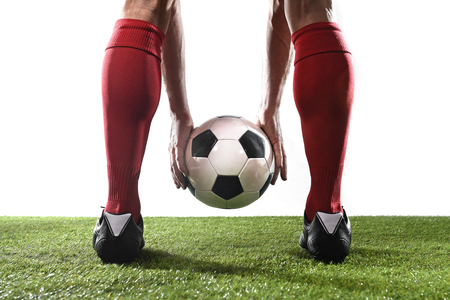 close up legs of football player in red socks and black shoes holding the ball in his hands placing it at the free kick or penalty spot playing on grass pitch isolated on white background