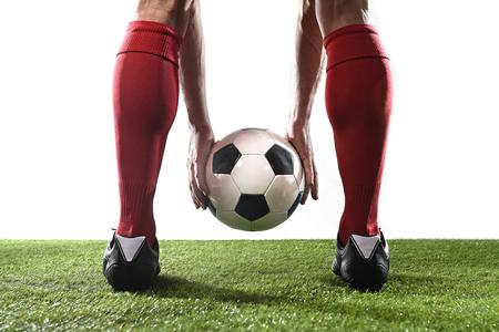 fermer les jambes du joueur de football dans des chaussettes rouges et chaussures noires tenant le ballon dans ses mains le plaçant au coup franc ou penalty en jouant sur terrain en gazon isolé sur fond blanc Banque d'images