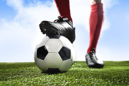 worldcup: close up legs and feet of football player in red socks and black shoes playing with typical ball standing on green grass pitch outdoors isolated on blue sky background Stock Photo