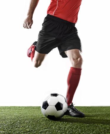 sportsman: cerrar las piernas de jugador de fútbol en medias rojas y zapatos negros corriendo y pateando la bola en la acción Tiro libre jugar aislados sobre fondo blanco