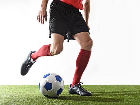 dribbling: close up legs and feet of football player in red socks and black shoes running and dribbling with the ball playing on green grass pitch isolated on white background