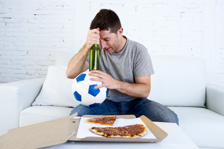 dejected: young soccer supporter man holding ball and beer bottle watching football game on television sitting at home couch looking dejected , sad and disappointed for failure or defeat Stock Photo