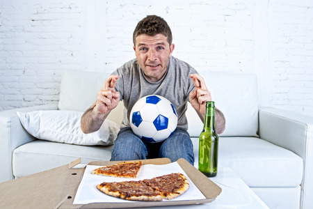 crossing fingers: young man alone in stress watching football game on television sitting at home living room sofa couch with ball , pizza box and beer bottle enjoying the match crossing fingers excited Stock Photo