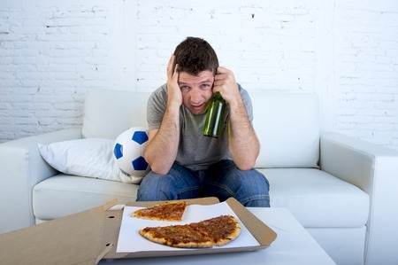 dejected: young supporter man with ball pizza and beer bottle watching football game on television sitting at home couch covering his eyes sad dejected and disappointed for failure or defeat Stock Photo