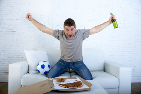 cheerfull: young man watching football game on television celebrating goal crazy happy jumping on sofa couch at home with ball beer bottle and pizza looking excited and cheerfull