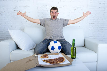 young man watching football game on television celebrating goal crazy happy jumping on sofa couch at home with ball beer bottle and pizza looking excited and cheerfull