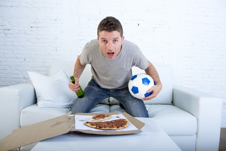 disbelief: young man alone holding ball and beer bottle in stress watching football game on television at home living room sofa couch with pizza box excited and in disbelief face expression Stock Photo