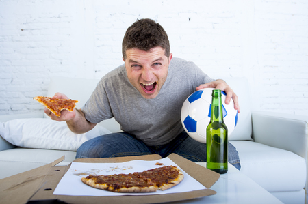 cheerfull: young man watching football game on television celebrating goal crazy happy sitting on sofa couch at home holding and pizza with beer bottle looking excited and cheerfull Stock Photo