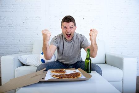 junger Mann vor dem Fußballspiel im Fernsehen Ziel verrückt glücklich feiern auf dem Sofa Couch zu Hause mit Kugel springt Bierflasche und Pizza aufgeregt und cheer