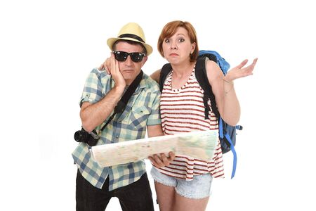 confused face: young tourist couple reading city map looking lost and confused loosing orientation with girl carrying travel backpack and man in frustrated face expression isolated white background Stock Photo