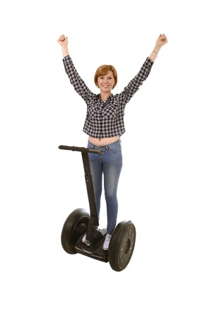 free riding: young attractive tourist woman rising arms up and free smiling happy riding electrical segway having fun driving isolated on white background in ecological transport concept