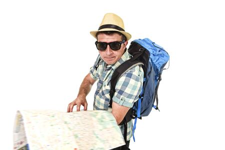 confused face: young tourist man reading city map looking lost and confused loosing orientation carrying backpack wearing summer hat and sunglasses disoriented  face expression isolated white background Stock Photo