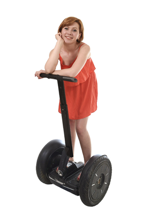 chic woman: young attractive tourist woman in chic summer dress smiling happy riding electrical segway having fun driving isolated on white background in ecological transport concept Stock Photo