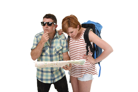 loosing: young tourist couple reading city map looking lost and confused loosing orientation with girl carrying travel backpack and man in frustrated face expression isolated white background Stock Photo