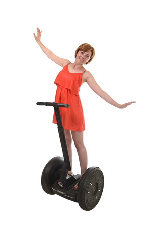 free riding: young attractive tourist woman in chic summer dress smiling happy hands free riding electrical segway having fun driving isolated on white background in ecological transport concept Stock Photo
