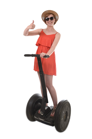 chic woman: young attractive tourist woman in chic summer dress smiling happy riding electrical segway giving thumb up having fun driving isolated on white background in ecological transport concept
