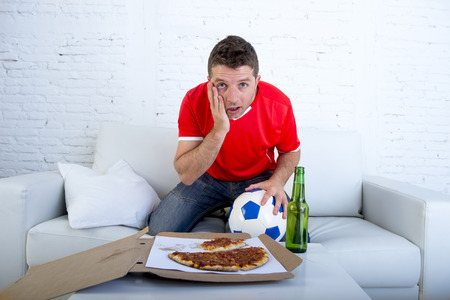 disbelief: young man alone holding ball with beer and pizza in stress wearing team jersey watching football game on television at home living room sofa couch excited in disbelief face expression