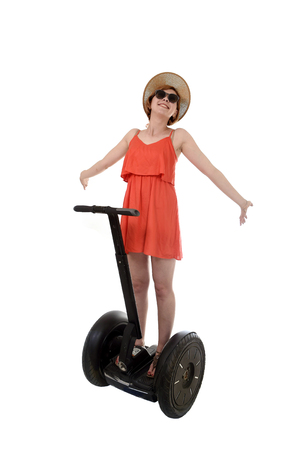 chic woman: young attractive tourist woman in chic summer dress smiling happy riding electrical segway having fun hands free driving isolated on white background in ecological transport concept