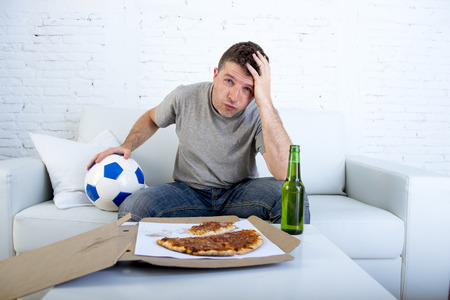 dejected: young supporter man with ball and pizza and beer bottle watching football game on television sitting at home couch in stress dejected and disappointed for failure or defeat
