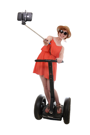 chic woman: young chic tourist woman taking selfie photo with mobile phone while riding on segway urban transport having fun isolated on white background in vacation tourism concept Stock Photo